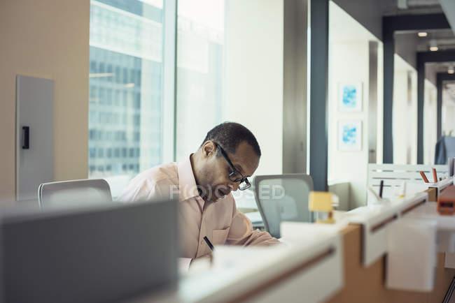 Konzentrierter Geschäftsmann, der allein im Büro arbeitet — Stockfoto