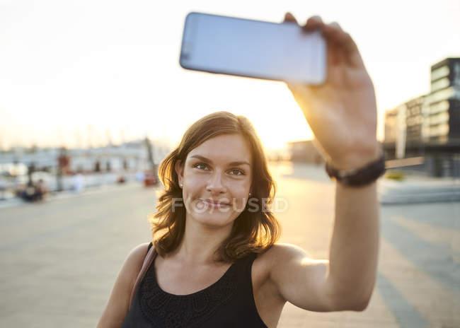 Deutschland, junge Frau in Hamburg nehmen Selfie mit ihrem Smartphone — Stockfoto