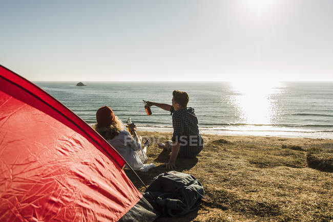 Pareja joven acampando en la playa bebiendo cerveza al atardecer - foto de stock
