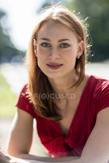 Portrait of cute redhead caucasian woman against blurred background — Stock Photo