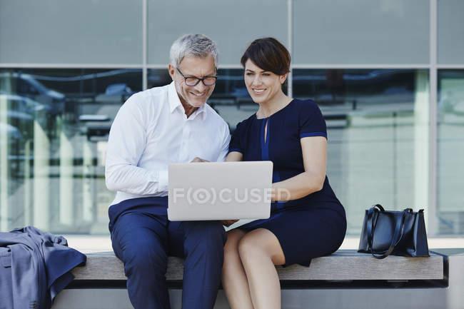 Бизнесмен, предприниматель, сидя на скамейке, обмена ноутбук — стоковое фото