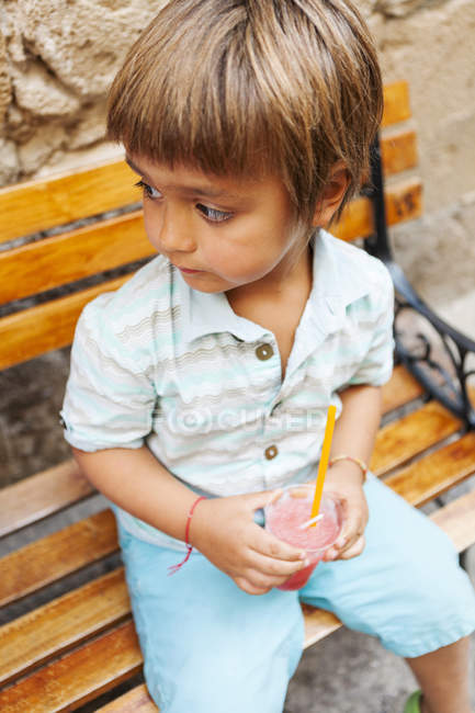 Little boy with cooled soft drink sitting on wooden bench — Stock Photo