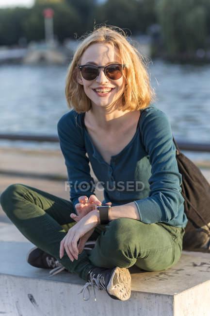 Jeune femme blonde séduisante avec smartwatch assis à l'extérieur — Photo de stock