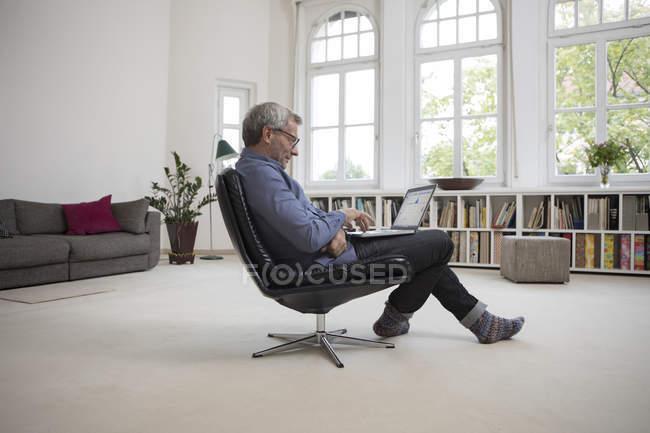Зрелый человек сидит в кресле и с помощью ноутбуков на дому — стоковое фото