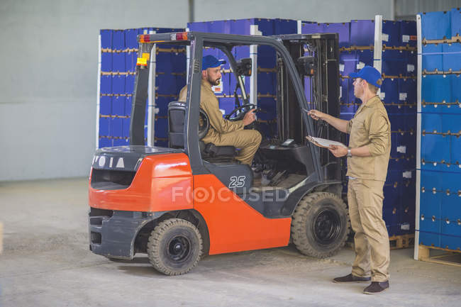 Charge de stockage des travailleurs avec chariot élévateur à fourche à la ferme orange — Photo de stock