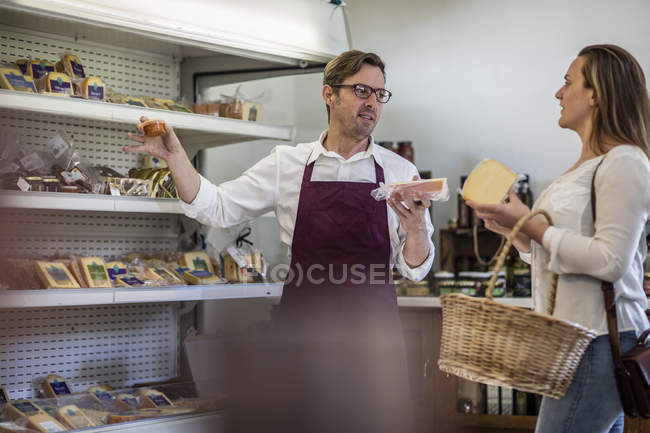 Grocer selling cheese in a grocery store — Stock Photo