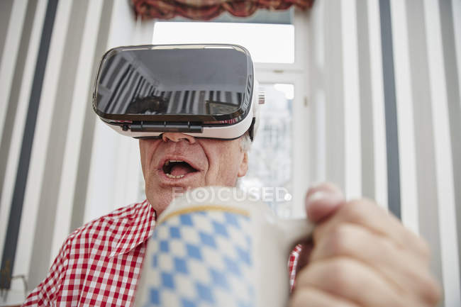 Старший чоловік тримає пивні гуртки в окулярах Vr — стокове фото