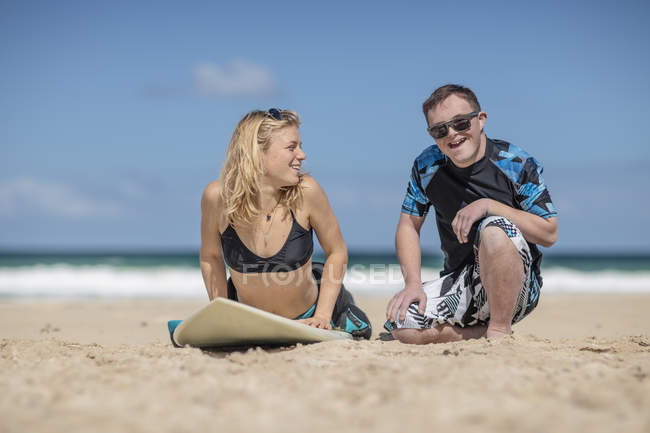 Teenage boy with down syndrome having surf lessons on beach — Stock Photo