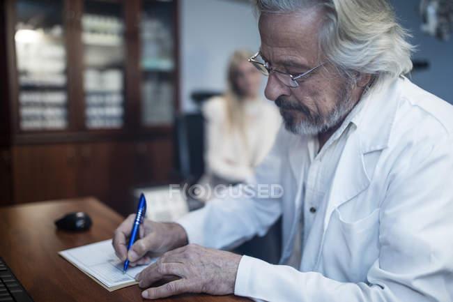Augenarzt schreibt Krankenakte des Patienten in Klinik — Stockfoto