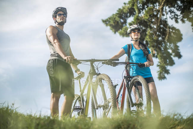 Young couple mountain biking in nature — Stock Photo