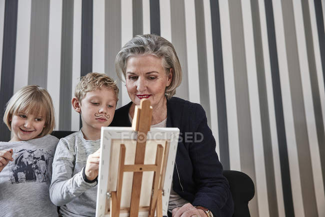 Grandmother and grandson with Dali moustache at easel with girl watching — Stock Photo