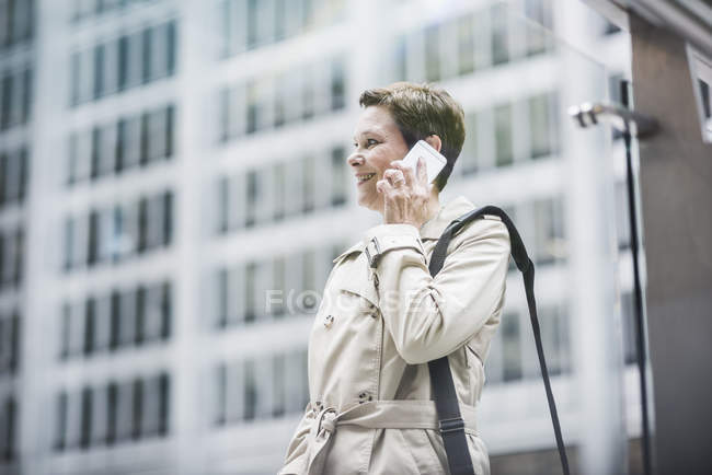 USA, New York City, smiling businesswoman in Manhattan on cell phone — Stock Photo