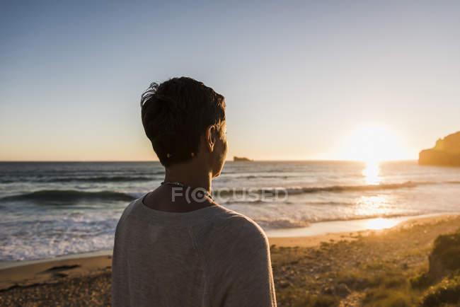 Nahaufnahme einer Frau, die bei Sonnenuntergang am Strand steht — Stockfoto