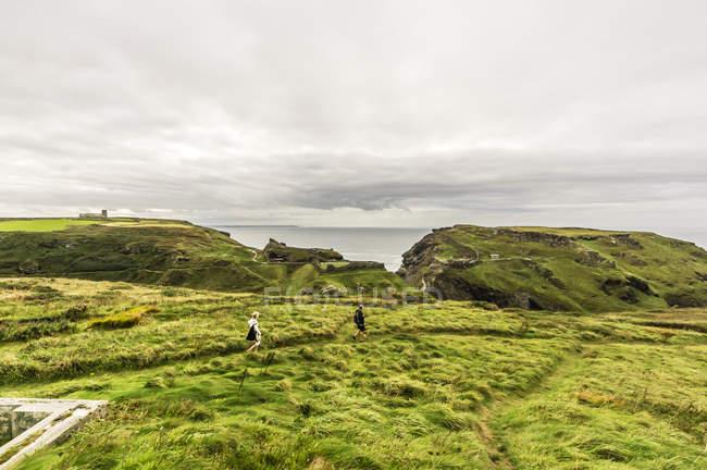 Reino Unido, Cornualha, Tintagel, turistas caminhando em montanhas verdes na costa — Fotografia de Stock