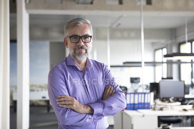 Портрет впевнено бізнесмен, стоячи в офісі з обіймами перетнула — стокове фото