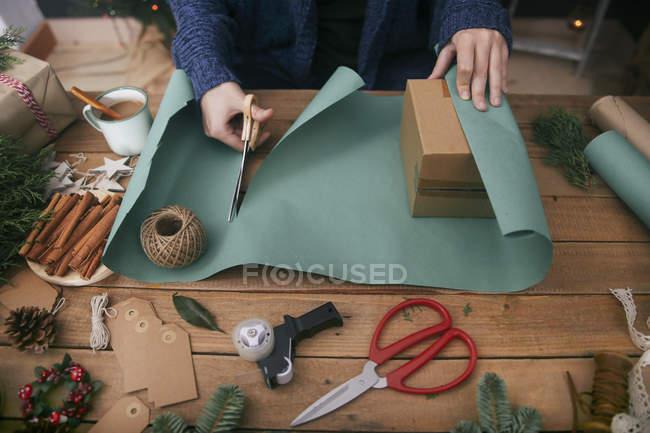 Mulher embrulhando presentes de Natal na mesa com objetos decorativos — Fotografia de Stock