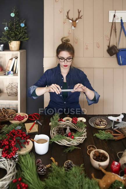 Woman taking picture of self-made Advent wreath with smartphone — Stock Photo