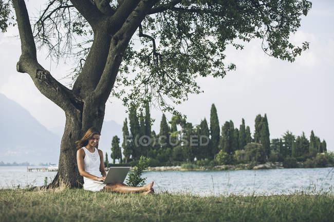 Італія, озеро Гарда, молода жінка, притулившись дерево, використовуючи ноутбук — стокове фото