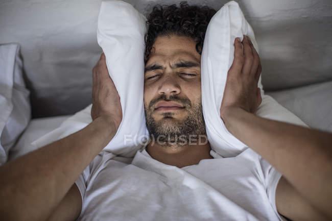 Jovem, cobrindo seus ouvidos com um travesseiro — Fotografia de Stock