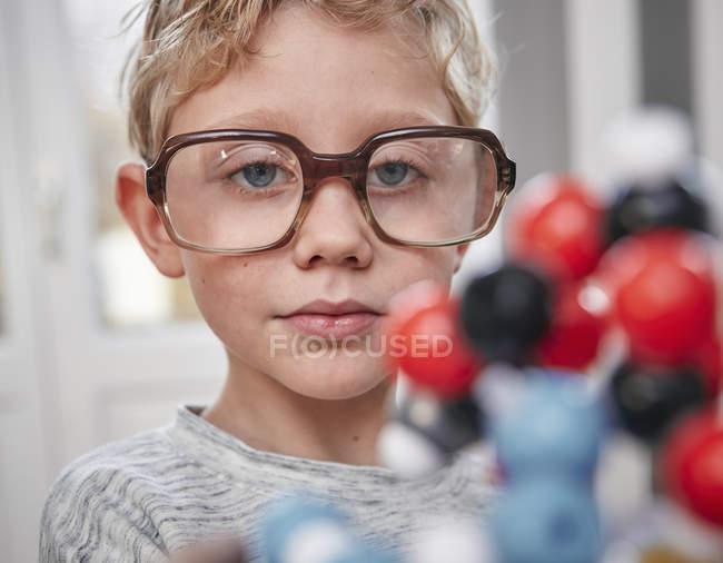 Garçon, lunettes surdimensionnées, regarde le modèle moléculaire — Photo de stock