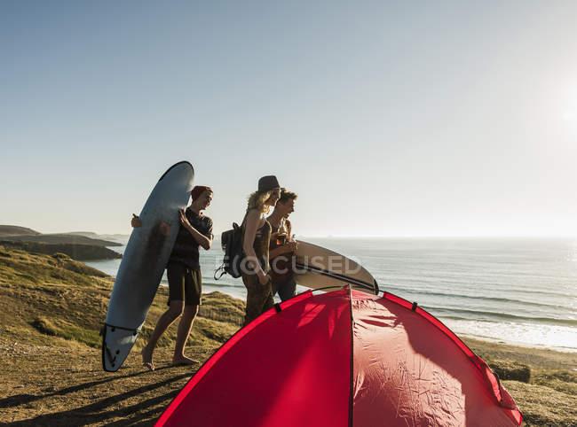 Três amigos com pranchas de surf camping na beira-mar — Fotografia de Stock