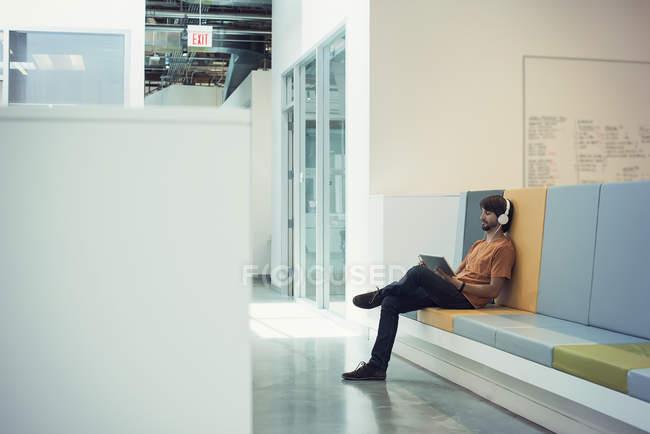 Молодий підприємець використання навушників і цифровий планшет, сидячи на лавці з — стокове фото