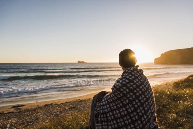Donna seduta avvolta in una coperta sulla costa al tramonto — Foto stock