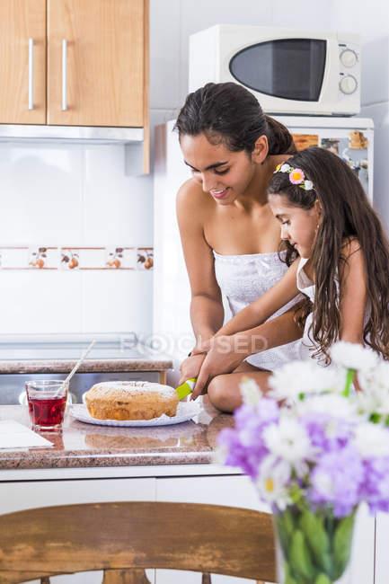 Adolescente e a irmã na cozinha cortando um bolo — Fotografia de Stock