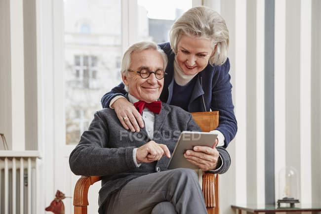 Smiling senior couple using tablet — Stock Photo