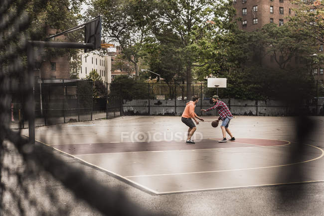 Dois homens jovens jogando basquete na quadra ao ar livre — Fotografia de Stock
