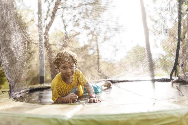 Lächelnder kleiner Junge auf Trampolin liegend — Stockfoto