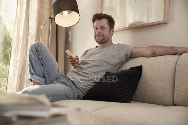 Entspannter Mann sitzt zu Hause mit Handy auf Couch — Stockfoto