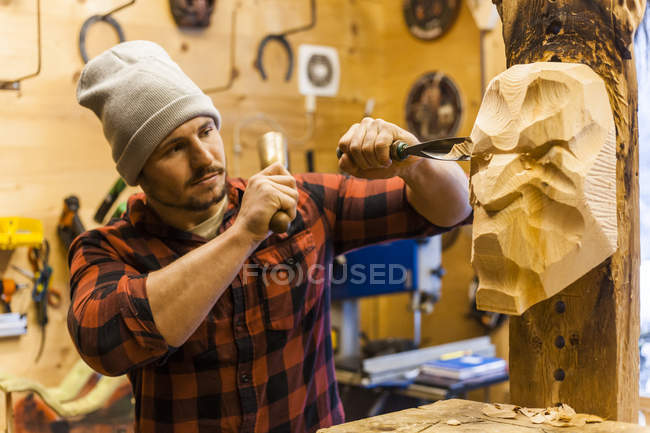 Wood carver manufacturing traditional Krampus mask — Stock Photo