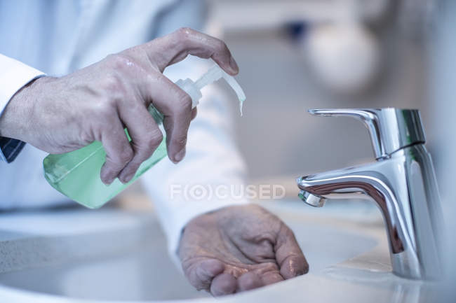 Professional caucasian doctor washing hands with soap — Stock Photo
