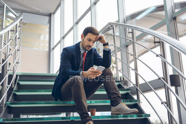 Pensive businessmann sitting on stairs looking at cell phone — Stock Photo