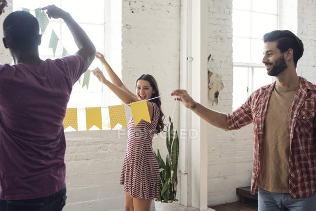 Friends hanging up bunting together — Stock Photo