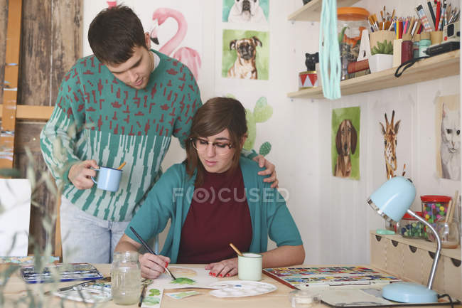 Artist painting in her studio while her boyfriend watching her — Stock Photo