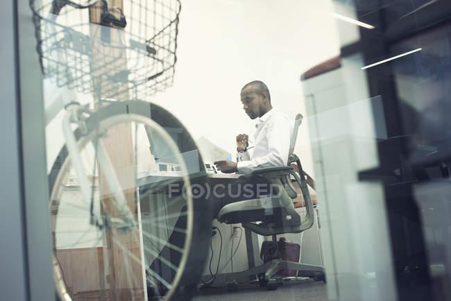 Білий комірець працівник, сидячи в офісі, дивлячись на смарт-телефон — стокове фото
