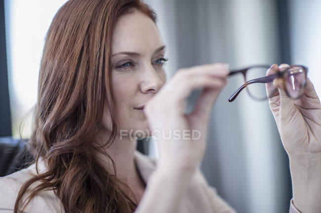 Businesswoman looking at her glasses — Stock Photo
