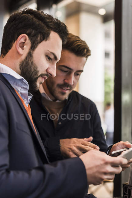 Dois empresários verificar dispositivos móveis — Fotografia de Stock