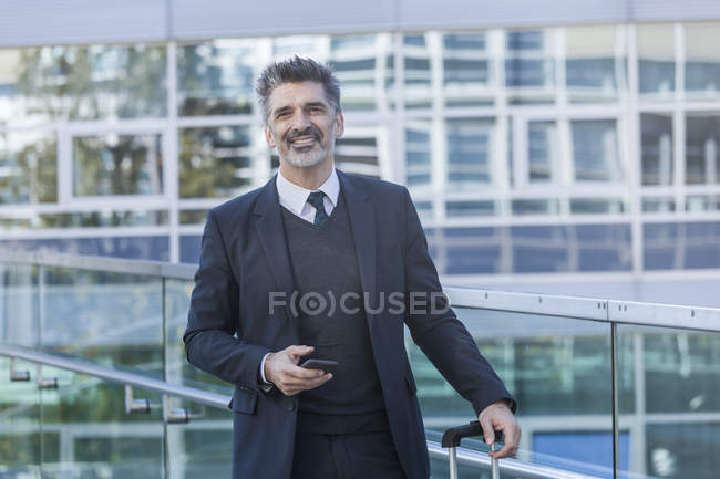 Portrait of smiling businessman standing with cell phone — Stock Photo
