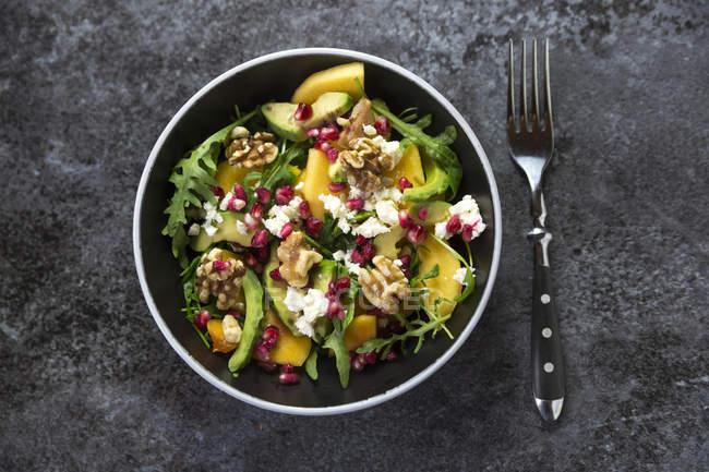 Bowl of avocado salad with rocket, pomegranate seed, kaki, feta and walnuts — Stock Photo