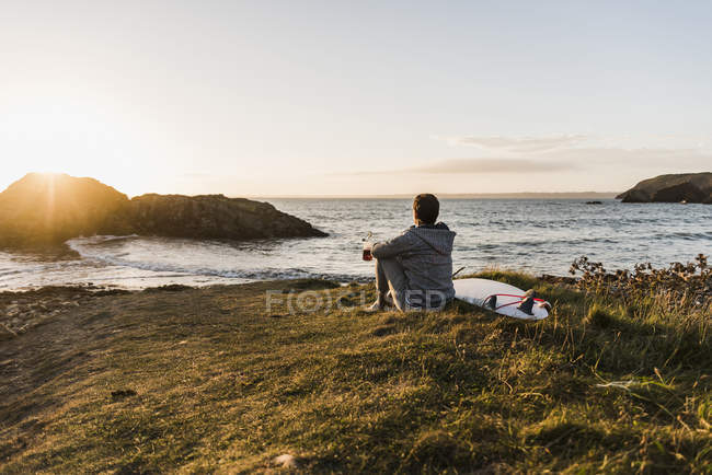 Woman sitting at the coast at sunset with surfboard — Stock Photo