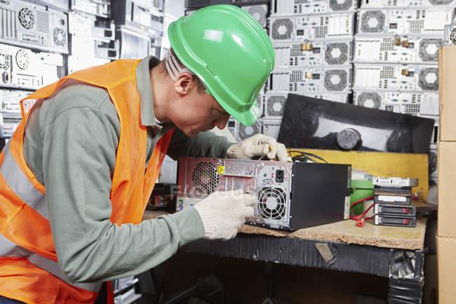 Travailleur dans l'usine de recyclage informatique ouverture de boîtier PC — Photo de stock