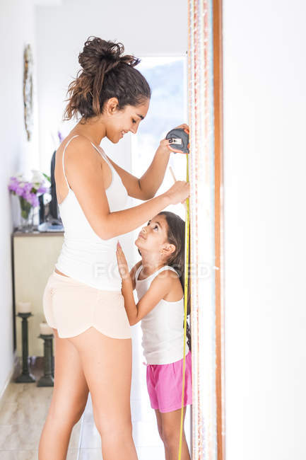 Teenage girl measuring her little sister at home — Stock Photo