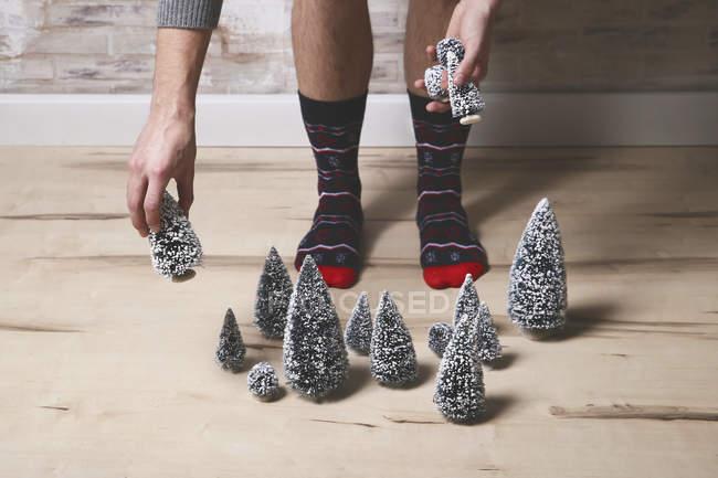 Молодой человек в зимних носках кладет елку украшения на пол — стоковое фото