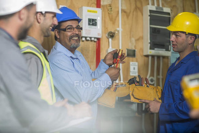 Electrician instructor explaining tools to students — Stock Photo