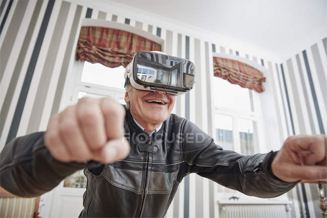 Senior man in motorcycle suit wearing VR glasses — Stock Photo