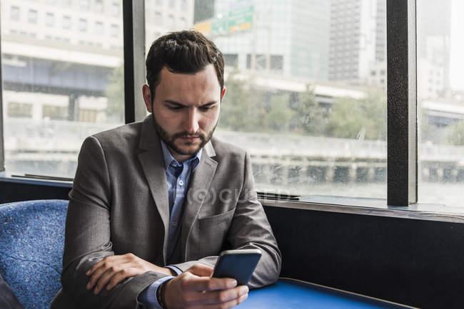 Empresário na plataforma de passageiros do ferry verificando o telefone celular — Fotografia de Stock