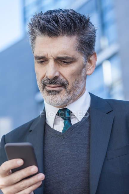 Homem de negócios usando o telefone celular ao ar livre — Fotografia de Stock
